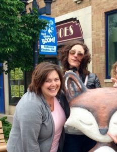 Me and a friend posing with a fox statue. I am leaning forward, lauging, trying to make sure everyone is in the shot
