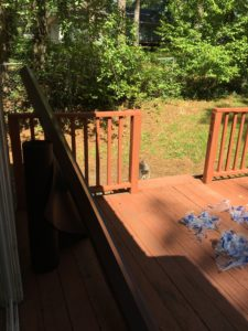 A half shaded deck with plastic wrap desbris, and a long piece of metal roof flasing propped on the deck rail