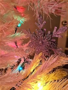 close up of a snowflake shaped oranment on a white christmas tree with colored lights around