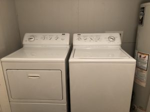 Top load washer on the right, dryer on the left next to a water heater