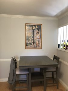 gray pub height kitchen table with two chairs against a light gray wall with a white chair rail and below a travel poster advertising Cuba