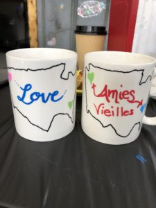 two coffe mugs with an outline of the us. Hearts in the pacific north west and north carolina regions. one says love in the middle of the country the other 'old friends' in french.