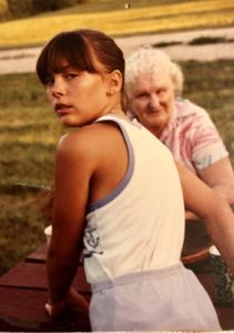 Young girl with dark brown hair looking back over her shoulder. Older woman in the background looking at her.