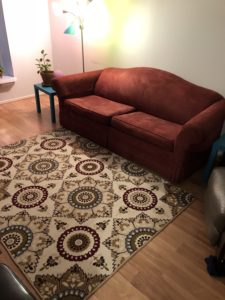 Rust red couch next to coordinating rug, framed by aqua end tables and grey leather recliner