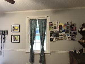 Window framed by corkboard full of post cards on right and two framed pictures on the left.