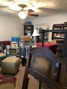 Room filled with the stuff of moving, boxes, a wooden bedframe, mattress, box spring, etc.