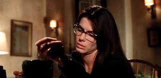 Sandra Bullock from Practical Magic. Wearing Glasses, concentrating on a spell