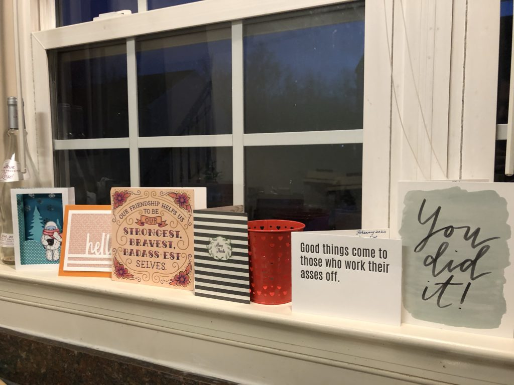 a line of inspirational cards propped on a window sill