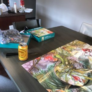 Grey kitchen table. Watercolor style poster of a mermaid laid out on the table next to a can of sparkling water and an open jigsaw puzzle box.