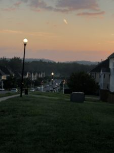 a dark street, looking across a neighborhood to hills with a sky lightening from purple to orange as the sun comes up